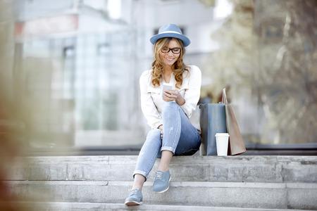 taza cafe: Mujer joven feliz con una taza de café y de compras bolsas desechables que se sienta en las escaleras y el uso de su teléfono inteligente para la comunicación a través de internet wifi en un parque de verano. Foto de archivo