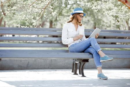 Estudiante joven feliz con una tableta y una taza de café desechables sentado en el banco y la lectura en un parque de verano.