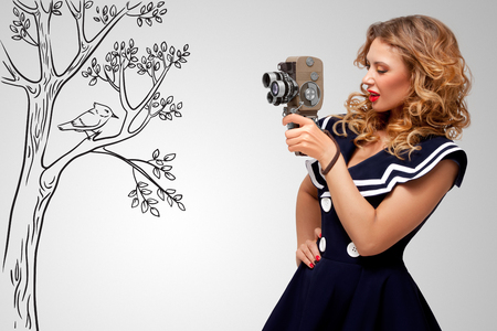 camera girl: Glamorous pin-up sailor girl filming nature and wildlife with an old retro cinema 8 mm camera, standing in front of a bird on grey sketchy background.
