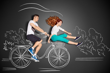 Gelukkig Valentijnsdag liefde verhaal concept van een romantische paar tegen krijttekeningen achtergrond. Man rijdt zijn vriendin in een front fietsmand. Stockfoto