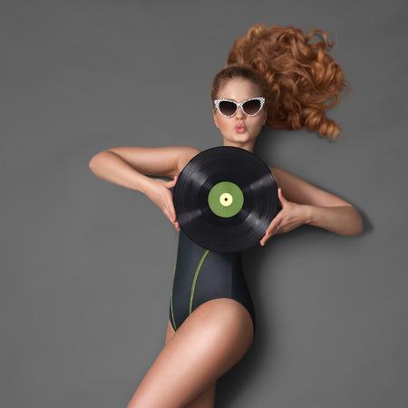 jovenes enamorados: Hermosa chica en bikini y gafas de sol, sosteniendo un disco de vinilo LP microsurco y enviando un beso en fondo de pizarra.