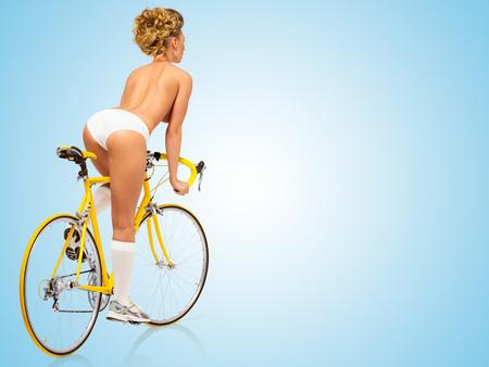 Retro foto van een naakt sexy pin-up girl in wit slipje rijden op een gele racefiets op een blauwe achtergrond.