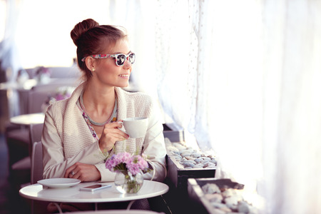 Photo of a beautiful happy young woman with smartphone and sunglasses, drinking hot tea or coffee on a cafe patio and looking out the window. Stock Photo
