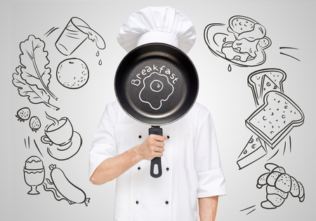 hot announcement: Restaurant chef hiding behind a frying pan with sketchy fried eggs for breakfast menu.