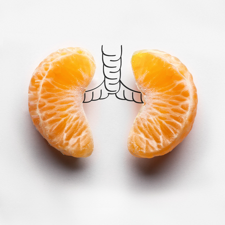 A health concept of unhealthy human lungs of a smoker with lung cancer in dark shadows, made of mandarin segments. Archivio Fotografico