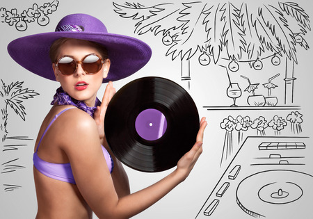 party system: Colorful photo of a beautiful deejay in bikini holding a retro vinyl record in her hands on sketchy background of a DJ mixer and exotic landscape.