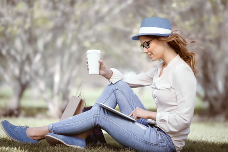 using tablet: Happy young woman a disposable coffee cup sitting on the grass and using touch pad on her tablet in a summer park. Stock Photo