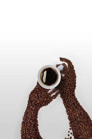 coffee beans: Creative coffee bean art; human hands made of roasted coffee beans, holding a coffee cup on grey background.