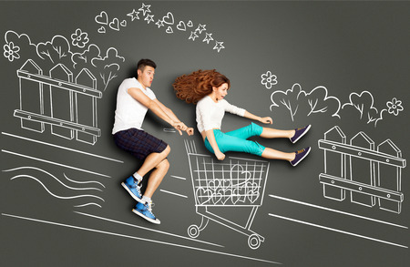 Happy valentines love story concept of a romantic couple on chalk drawings background. Male riding his girlfriend in a shopping cart along the street.