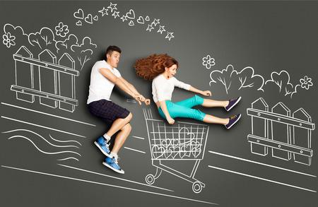 Happy valentines encanta concepto historia de una pareja romántica en dibujos de tiza de fondo. Hombre que monta su novia en un carro de compras a lo largo de la calle. Foto de archivo - 50775365