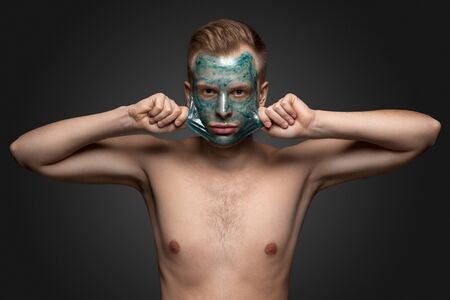 peel: Portrait of a beautiful young man peeling off a facial mask, face and body skin care retreat.