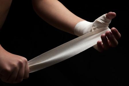 wraps: boxeador de sexo femenino hermoso y el ajuste está preparando para la lucha o la formación, envolviendo sus manos con cinta de vendaje contra el fondo oscuro.