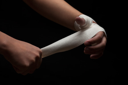 revenge: Beautiful and fit female fighter getting prepared for the fight or training, wrapping her hands with bandage tape against dark background.