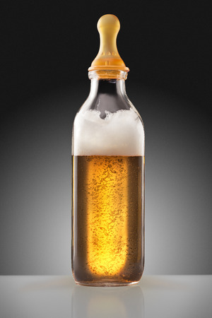 drinking milk: A feeding bottle with nipple full of beer as a milk replacement for babies. Stock Photo