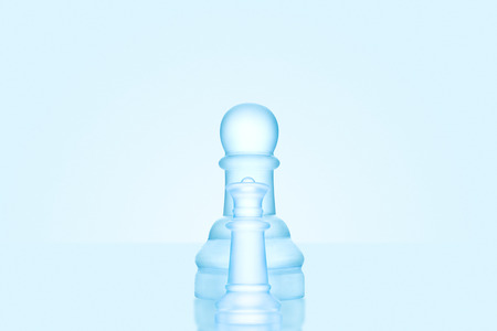 outwit: Chess game concept of a single icy frosted pawn standing alone on glacial chessboard.