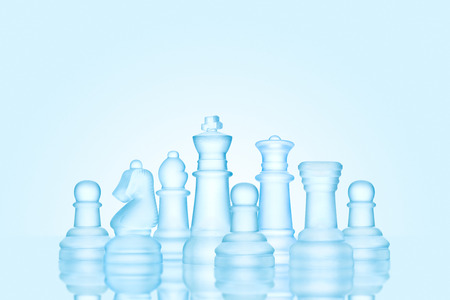 strong strategy: Strategy and leadership concept; frosted chess figures made of ice, standing together as a family ready for game. Stock Photo