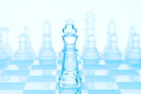 concept de jeu d'échecs d'un roi givré glace debout devant les pièces d'échecs sur l'échiquier glaciaire.