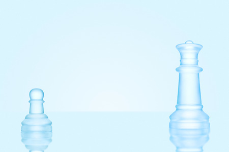 outwit: Leadership and bravery concept; an icy frosted single pawn staying against a queen on chessboard.