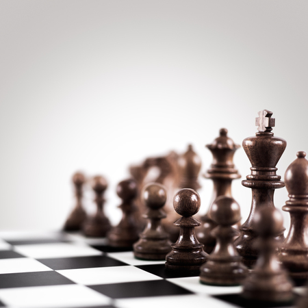 outwit: Strategy and tactics concept; black wooden chess figures on the board standing in a row ready for game. Stock Photo
