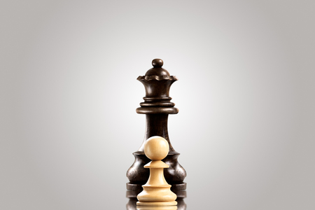 outwit: Leadership and bravery concept; white wooden single pawn staying against a black queen.