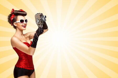 old style retro: Retro photo of a glamorous pin-up girl with an old vintage cinema 8 mm camera shooting a movie on colorful abstract cartoon style background.