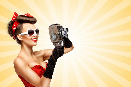 old style retro: Glamorous vintage pin-up girl filming movie with an old retro cinema 8 mm camera, standing on colorful abstract cartoon style background.