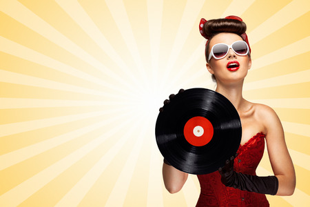 melomaniac: Vintage photo of glamorous pinup girl wearing long gloves and dressed in a red sexy corset, holding LP vinyl record on colorful abstract cartoon style background. Stock Photo