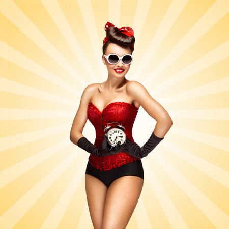 glamorous: Glamorous pinup girl in a red vintage corset holding a retro alarm clock in her hand and smiling on colorful abstract cartoon style background.