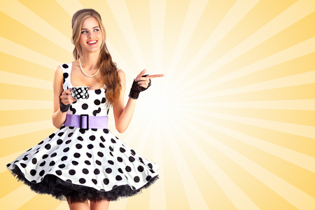 aside: Creative vintage photo of a beautiful pin-up girl in a polka dot dress, holding a cup of tea and pointing aside on colorful abstract cartoon style background. Stock Photo