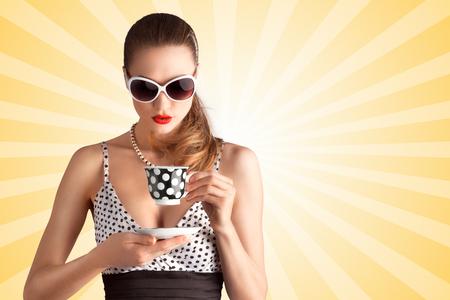 sexy bikini girl: Creative vintage photo of a beautiful pin-up girl in a polka dot bikini and sunglasses, drinking tea or coffee on colorful abstract cartoon style background.