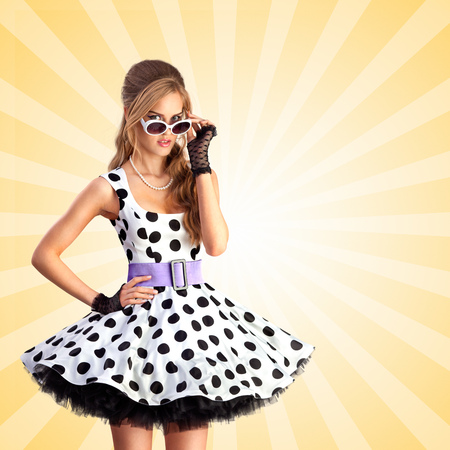 vogue: Creative photo of a vogue pin-up girl, dressed in a retro polka-dot dress and sunglasses, posing on colorful abstract cartoon style background. Stock Photo