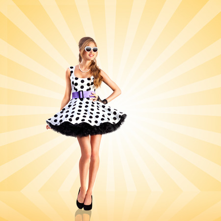 Creative photo of a vogue pin-up girl, dressed in a retro polka-dot dress and sunglasses, posing on colorful abstract cartoon style background. Stok Fotoğraf