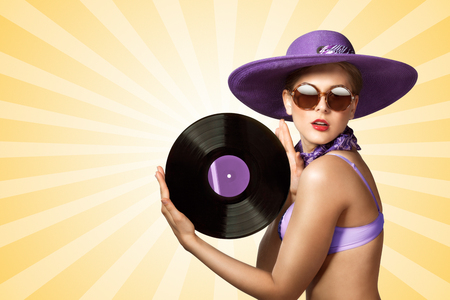 playback: Beautiful pinup bikini model wearing sunglasses and hat, holding an LP microgroove vinyl record on colorful abstract cartoon style background.