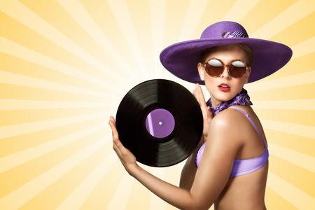 bikini model: Beautiful pinup bikini model wearing sunglasses and hat, holding an LP microgroove vinyl record on colorful abstract cartoon style background.