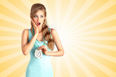 woman shock: Creative photo of a shocked pin-up girl being late and holding a retro alarm clock on colorful abstract cartoon style background.