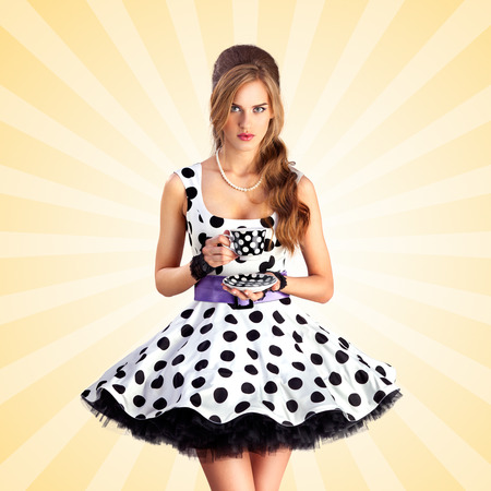 manners: Creative vintage photo of a beautiful pin-up girl in a polka dot dress, holding a cup of tea on colorful abstract cartoon style background. Stock Photo