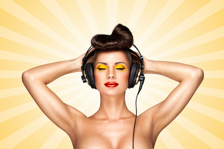 nude girl: Retro photo of a nude pin-up girl with big vintage music headphones on colorful abstract cartoon style background.