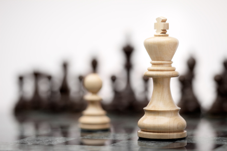 outwit: Leadership and bravery concept; white wooden single pawn staying against a white king on chessboard.