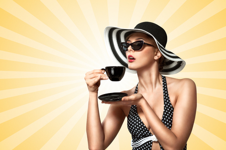 manners: A creative vintage photo of a beautiful pin-up girl drinking tea and showing good table manners on colorful abstract cartoon style background.