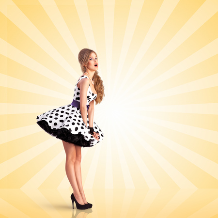 colorful dress: Creative vintage photo of a smiling pin-up girl wearing a retro polka-dot dress on colorful abstract cartoon style background.