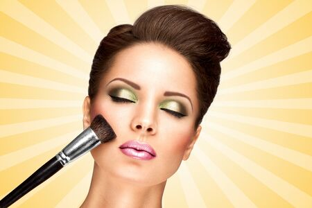 cosmetician: Glamour girl with retro fashion hairstyle applying dry cosmetic tonal foundation on the face using makeup brush on colorful abstract cartoon style background. Stock Photo