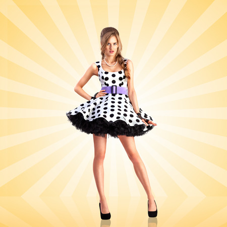 vogue: Creative photo of a vogue pin-up girl, dressed in a retro polka-dot dress, posing on colorful abstract cartoon style background.