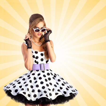 retro woman: Creative photo of a vogue pin-up girl, dressed in a retro polka-dot dress and sunglasses, posing on colorful abstract cartoon style background. Stock Photo