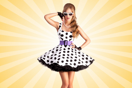 fashion dress: Creative photo of a vogue pin-up girl, dressed in a retro polka-dot dress and sunglasses, posing on colorful abstract cartoon style background. Stock Photo