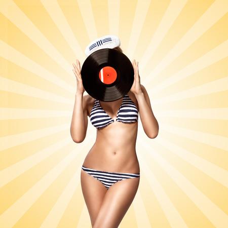 bikini model: Beautiful pinup bikini model, hiding behind an LP microgroove vinyl record on colorful abstract cartoon style background.