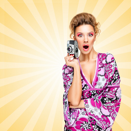 homemaker: Retro photo of an amazed fashionable hippie homemaker with an old vintage photo camera showing emotions on colorful abstract cartoon style background.