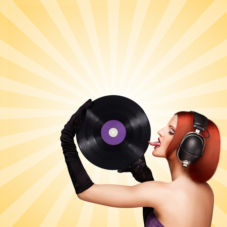 licking: Colorful photo of a seductive girl, wearing huge vintage music headphones and licking a purple LP microgroove vinyl record on colorful abstract cartoon style background. Stock Photo