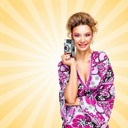 old style retro: Retro photo of a happy fashionable hippie homemaker with an old vintage photo camera smiling on colorful abstract cartoon style background.