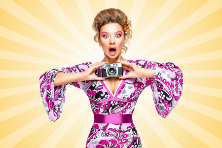 homemaker: Retro photo of an amazed fashionable hippie homemaker, holding an old vintage photo camera with two hands and showing emotions on colorful abstract cartoon style background. Stock Photo