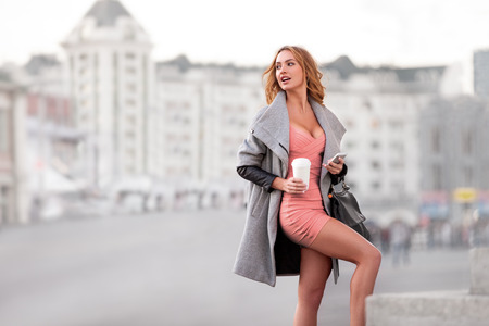 urban scene: A businesswoman with a mobile phone holding a coffee cup against urban scene.